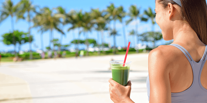 Woman holding a glass of green juice while outside